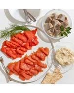 An Acme Smoked Fish collection of smoked wild sockeye salmon, pickled herring, smoked organic salmon, and smoked whitefish salad.