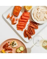 An Acme Smoked Fish collection of honey maple smoked salmon, classic smoked salmon, whitefish salad, and smoked salmon candy.